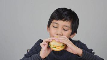 niño asiático comiendo una deliciosa hamburguesa video