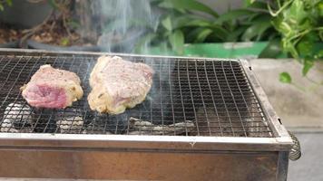 Grillen Sie das Rindfleisch auf dem Holzkohlegrill, um Steaks zuzubereiten. video