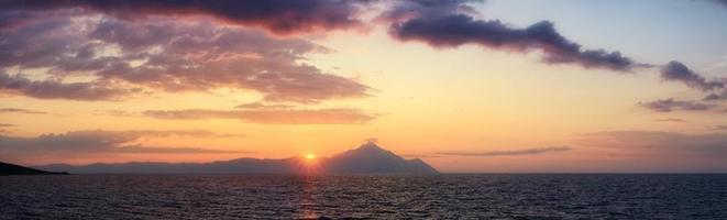 Scenic sunrise at Sarti beach, Halkidiki, Sithonia, Greece, Europe. Golden sunrise over the mountain Athos, dramatic morning seascape of the Aegean sea. photo