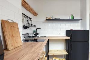 Attic apartment, modern kitchen, apartment interior design with old rustic wooden beams and furniture, stylish Italian granite ceramica. photo