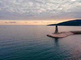 Aerial view of lighthouse at Lustica Bay in Montenegro at sunset light photo