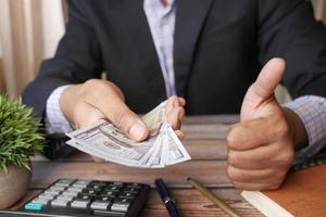 Unrecognized businessman hand counting 100 US dollars photo