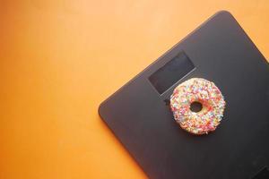 Donuts dulces en escala de peso sobre fondo naranja foto