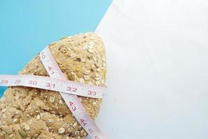 Slice of whole meal bread and measurement tape on table photo