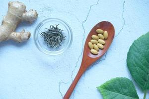 Herbal medicine on spoon and herbs on table photo