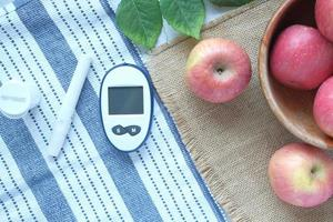 Herramientas de medición para diabéticos y manzana fresca en la mesa foto