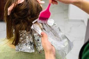 inicio de la coloración del cabello, técnica de coloración balayag, decoloración del cabello para aplicar pintura. foto
