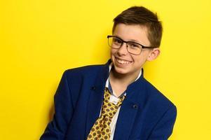 chico atractivo en un traje de adulto sobre un fondo amarillo, la imaginación de un niño sobre la vida adulta. foto