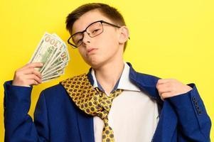 un tipo con un gran traje clásico sobre un fondo amarillo sostiene una moneda extranjera, un niño con gafas y un traje con corbata. foto