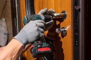 The master worker installs a door lock in the front door, metal doors with a polymer coating. photo