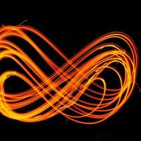 Abstract fiery pattern in the shape of the number 8. Drawing shapes with fire at night, infinity sign, bright colors on night background, fun with fire. photo