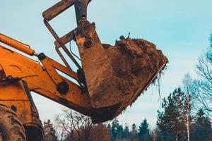 Closeup of a large bucket excavator digging the ground to set the road. photo