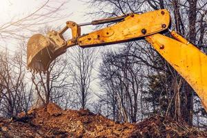 A yellow old excavator in the middle of the forest digs a ladle pit to collect water. photo