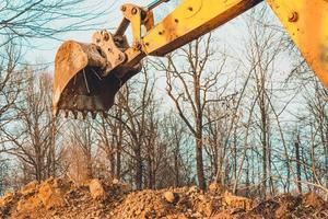 The excavator performs excavation work by digging the ground with a bucket in the forest. photo
