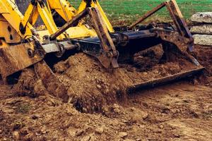 A close-up excavator loads soil into the bucket for further road installation. photo