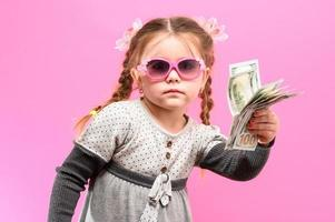 Little girl in glasses with a package and money on a pink background, child and shopping. photo