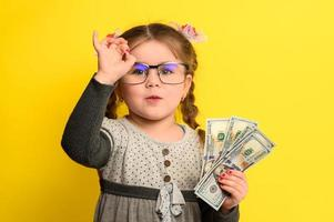 A beautiful girl is surprised by so much money, a child and big money. photo