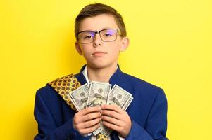 A boy in glasses and an oversized suit with a satisfied face is holding US dollars, a child and big money. photo
