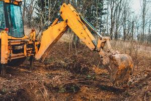 The excavator digs soil into the forest and uproots the roots of the trees. photo
