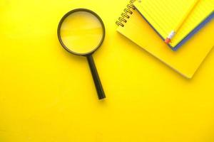 Open book and magnifying glass on yellow background photo