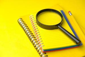 Open notepad and magnifying glass on yellow background photo