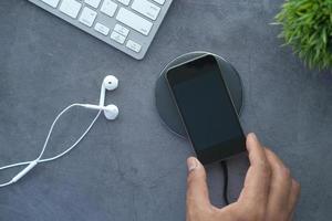 La mano del hombre cargando el teléfono inteligente con la plataforma de carga inalámbrica, vista superior foto
