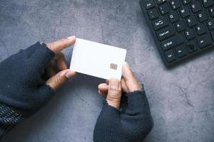 Hacker's hand stealing data from credit card photo