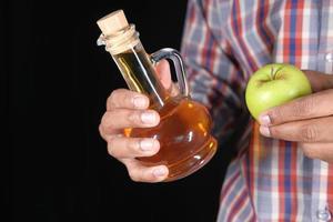 Hand holding apple vinegar in glass bottle with fresh green apple photo