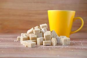 Taza de café amarilla y terrones de azúcar morena en la mesa foto