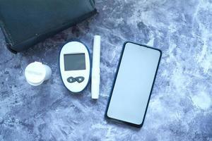 Herramientas de medición de diabetes y teléfono inteligente con pantalla vacía. foto