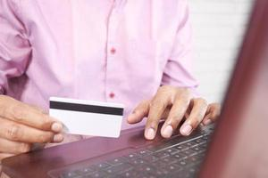 Man's hands holding credit card and using laptop shopping online photo