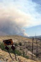 Billowing smoke from current Gila National Forest Johnson fire behind curved road sign in old burn photo