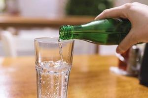 Pouring mineral water into the glass photo
