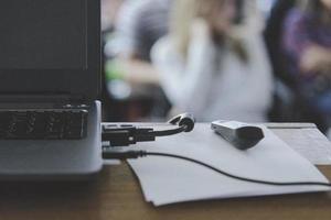 portátil en el escritorio de presentación de negocios con gente borrosa bokeh de fondo. foto