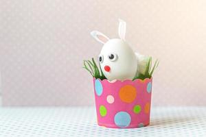 White chicken egg with bunny ears and a muzzle in an environmentally friendly pink paper tray photo