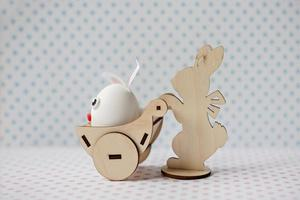 A wooden rabbit carries a cart with an egg with bunny ears photo