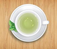 White cup of green tea on saucer stand on wooden table. Top view vector