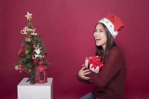 Beautiful Santa Claus girl in studio on red background, Christmas concept photo