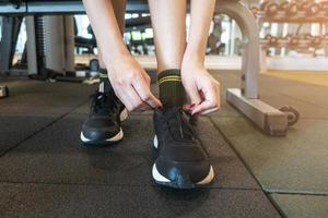 Close up woman tie up her shoe in gym photo