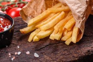 Sabrosas papas fritas frescas y salsa roja sobre una tabla de cortar de madera foto