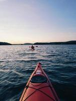 Red canoe or kayak in body of water during daytime photo