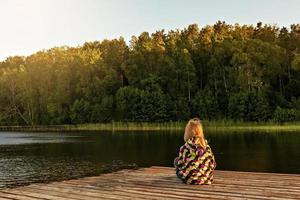 Little girl sits on a wooden pier on the lake at sunset in summer photo
