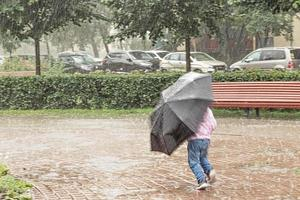 A little girl is having fun running around with an umbrella in the heavy rain photo
