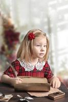 A little girl in a red dress is sitting at the table and writing a letter to Santa photo