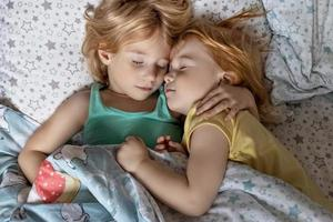 Two little sibling girls sisters sleeping in an embrace in bed under one blanket photo