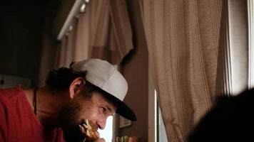 guy with a beard and a cap snapback eating a sandwich video
