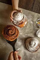 Children's hand takes a freshly baked cinnamon bun photo