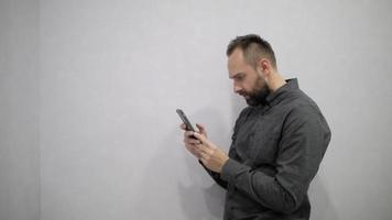 ein mann in hemd und bart schreibt sms ins telefon video