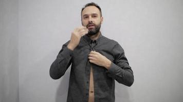 Man with a beard is buttoning his shirt video