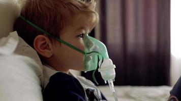 menino respira através da máscara transparente do inalador video